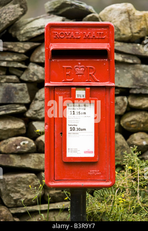 Traditional red Royal Mail post letter box and dry stone wall in rural England UK - Stock Photo