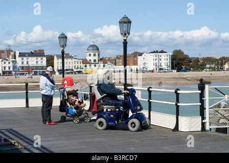 Mobility scooter user on the pier at Worthing West Sussex England - Stock Photo