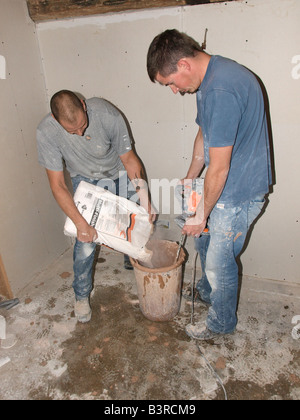 TWO PLASTERERS MIXING DRY PLASTER WITH WATER USING DRILL WITH PADDLE ATTACHED IN  CONTAINER. MIX USED FOR DRY LINED - Stock Photo