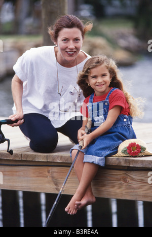 Mother teaching daughter how to fish, fishing trip, laughing, having fun together, Miami - Stock Photo