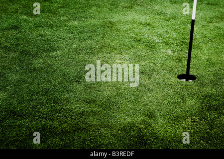 Golf course hole with pole - Stock Photo