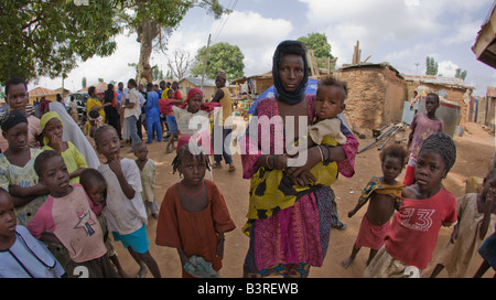 Wodaabe Fulani woman and children (carried and left) from Niger at a village near Abuja, Nigeria - Stock Photo