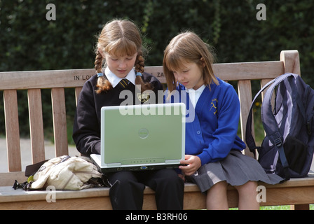 Two schoolgirls seated on a wooden bench using a laptop computer - Stock Photo