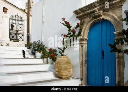 Door with carved stone surround and an old ceramic jar decorate a lane in Kythira town Kythira Greece - Stock Photo