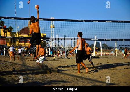 Young men playing a spirited game of volleyball at the beach near the Santa Cruz Boardwalk California - Stock Photo