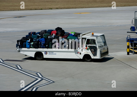 Baggage handler moving luggage at airport air side British Airport Jersey Channel Islands - Stock Photo