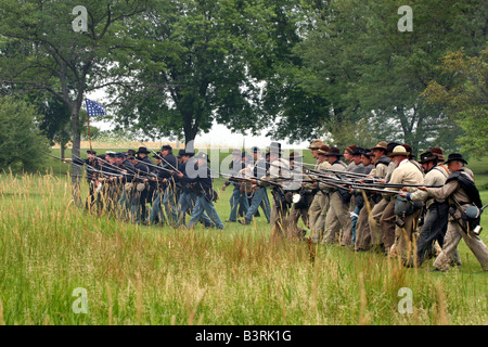Confederate and Union Soldiers advancing towards the crowd at a Civil War Encampment Reenactment - Stock Photo