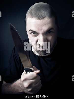 Ugly criminal with stockings over face and knife in his hand - Stock Photo