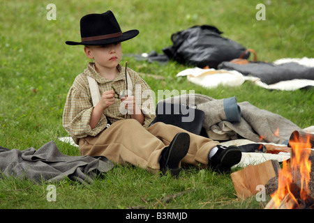 A boy in an 1850s outfit playing with a leaf by a campfire at a Civil War Encampment Reenactment - Stock Photo