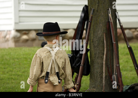 A boy near rifles leaning on a tree at a Civil War Encampment Reenactment - Stock Photo