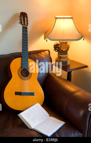 Guitar and book of music on sofa in living room - Stock Photo