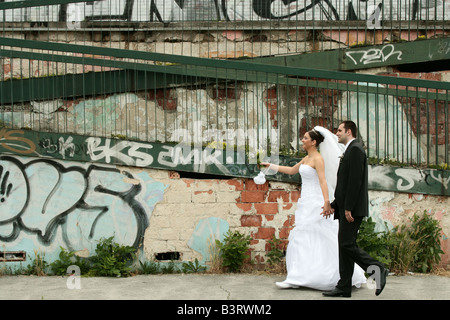 Rasto with his bride Zuzana pointing in front of a grffitti wall  Slovakia - Stock Photo