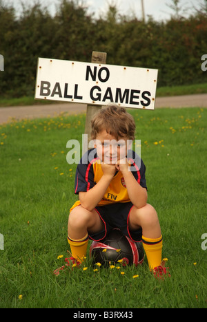Small boy and football wearing soccer team kit stands with a no ball games sign Nowhere to play - Stock Photo