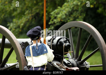 A young boy holding the union flag in front of a cannon at a Civil War Encampment Reenactment - Stock Photo