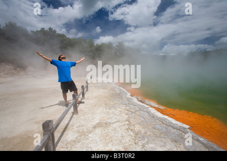 Man at Champagne Pool at geothermal site, Wai-O-Tapu Thermal Wonderland on North Island of New Zealand - Stock Photo