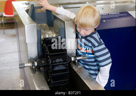 Child looking at interactive dispaly waterwheel at Stanley Mills visitor centre A historic cotton mill Perthshire - Stock Photo