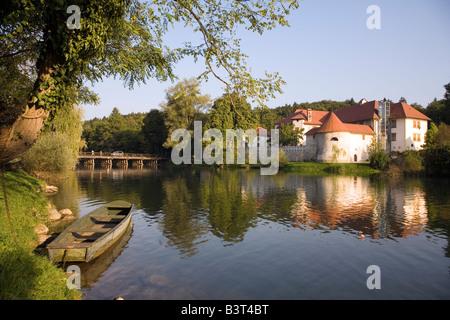 Boat and Castle Otocec on an isle of Krka River 7km from the town of Novo Mesto Dolenjska Slovenia Europe - Stock Photo