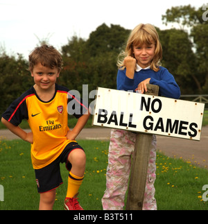Small boy wearing soccer team kit stands with a no ball games sign Nowhere to play for him or his sister - Stock Photo