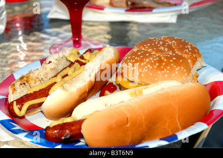 hot dogs and hamburger on american themed plate at out door bbq on labor day holiday - Stock Photo