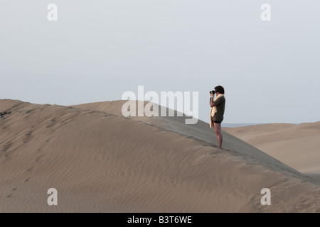 A woman in swimming trunks and stands on top of a sand dune taking photographs at dawn at Maspalomas, Gran Canaria - Stock Photo
