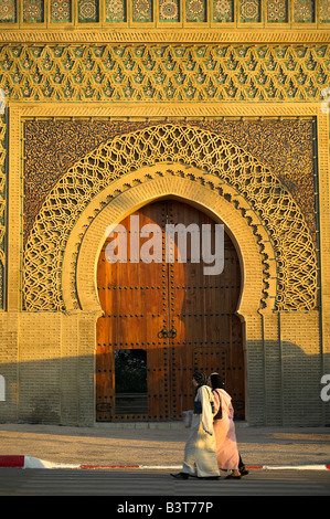 Two muslim women walk past the Bab el Mansour in Meknes, Morocco. Completed in 1732, it was once the main entrance - Stock Photo