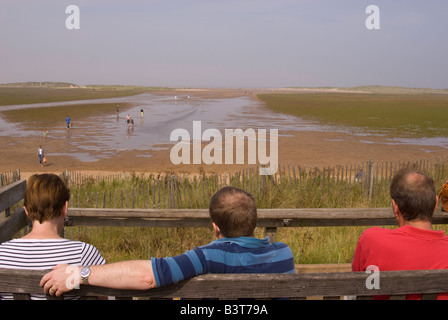 Three people sitting on bench looking out to Holkham Beach,Norfolk,Uk - Stock Photo