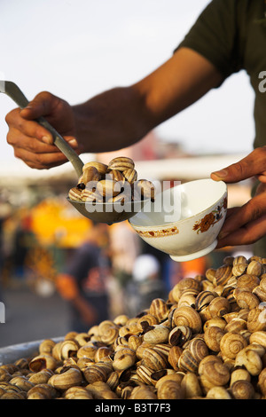 Morocco, Tangier. Snails for sale at one of the many food stalls that fill the Djemma el Fna in the evening. - Stock Photo