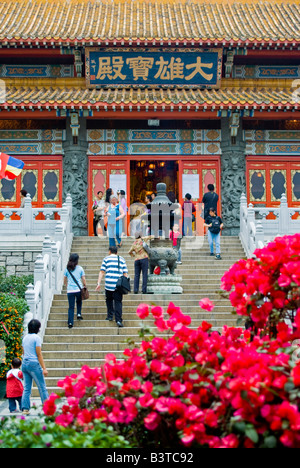 Asia, China, Hong Kong, Lantau Island. Worshippers enter the main temple of the Po Lin Monastery. - Stock Photo