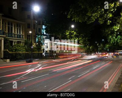 Streaks of light from traffic running down Park Lane London at night. - Stock Photo