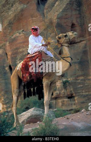 Asia, Jordan, Petra. Local man on camel near ruins. - Stock Photo