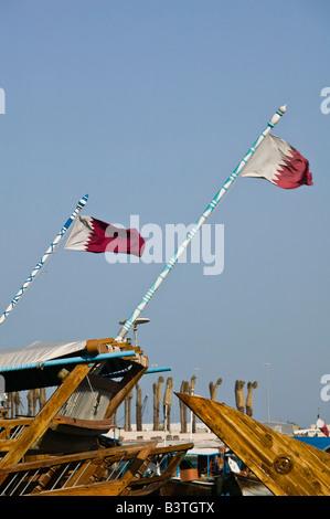 Qatar, Ad Dawhah, Doha. Dhow Harbor- Qatar Flag on Traditional Dhow Ships - Stock Photo