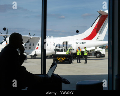 Man using laptop computer at London City Airport with Dornier 328 airplane in the background United Kingdom - Stock Photo