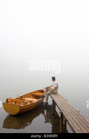 Man sitting on a landing stage at a misty morning in fall - Stock Photo