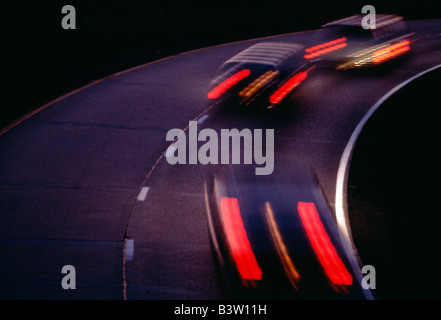 Blur of tail lights on moving cars at dusk - Stock Photo