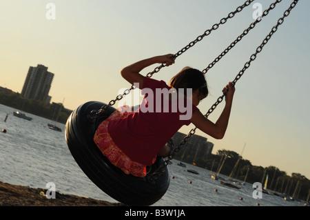 Girl in swing. - Stock Photo