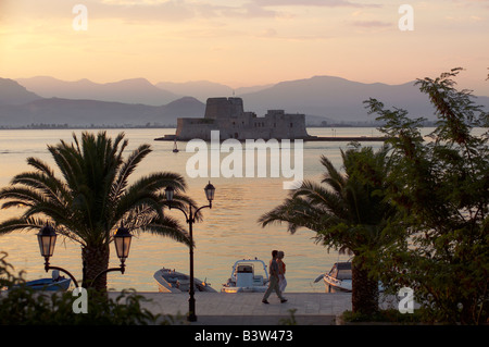Two people walk in front of Boats moored. Beyond is the water castle of Bourtzi. A Venetian castle located in the - Stock Photo