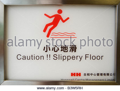 ' A sign in Hong Kong warning about a slippery floor.' - Stock Photo