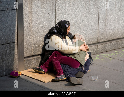 Beggars mother and daughter beg on streets in Paris France Europe EU - Stock Photo