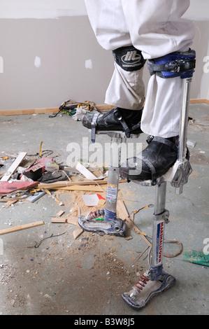 Man on stilts plastering ceiling - Stock Photo