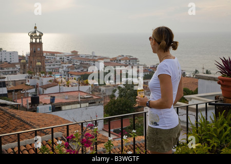 Mexico, Puerto Vallarta.  A woman drinking a beer and enjoying the view of the church Our Lady Guadalupe.  (MR) - Stock Photo