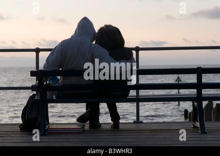 Young teenage couple wearing hoodies sitting and cuddling at sunset, Aberystwyth Wales UK, summer evening, seaside - Stock Photo