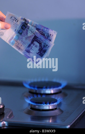 Woman burning british pounds on a gas hob - Stock Photo