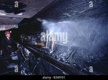 Coal miner operating a digging machine in a long wall mine - Stock Photo