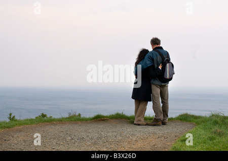 Couple Looking Out Over Clifftop View, Giants Causeway, Northern Ireland - Stock Photo