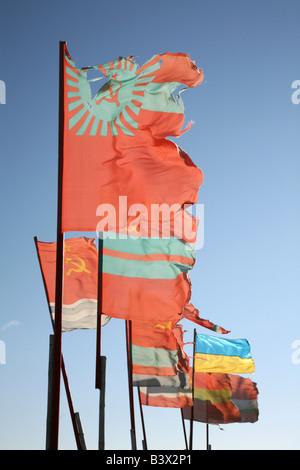 Old Soviet republics flags beside a modern Ukrainian flag waving over the pilgrim camp on the Solovetsky Islands, - Stock Photo