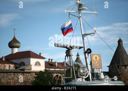 Russian flag and St Philip icon over the pilgrim ship in front of the Solovetsky Monastery in the White Sea, Russia - Stock Photo