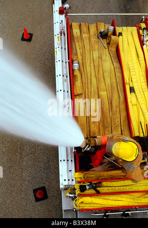 Overhead view of a fireman on a firetruck spraying water from a hose - Stock Photo