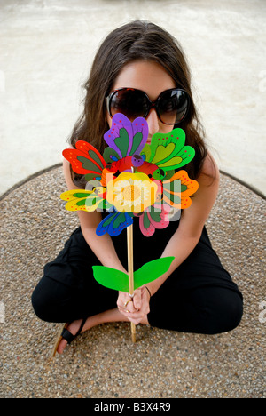 A brunette teenage girl wearing sunglasses hides behind a toy flower - Stock Photo