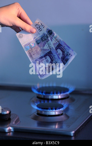 Woman burning british pounds on a gas hob - Stock Photo