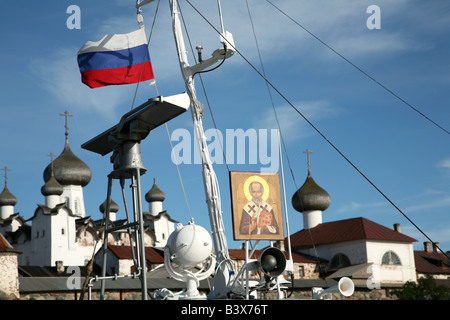 Russian flag and the icon of Saint Nicholas on the pilgrim ship in front of the Solovetsky Monastery in the White - Stock Photo